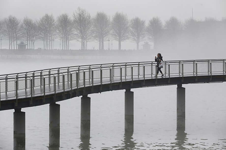A woman walks along a bridge at Frank Sinatra Park in Hoboken, N.J., as fog blankets over the Hudson River, Tuesday, April 8, 2014. (AP Photo/Julio Cortez)