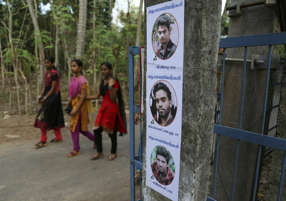 """Indian girls walk past posters displaying photographs of three friends, from top, Vishnu, Athiraj and Brijesh who died after a massive fire broke out Sunday during a fireworks display at the Puttingal temple complex in Paravoor village, Kollam district, southern Kerala state, India, Monday, April 11, 2016. Medical teams on Monday tended to hundreds of people injured in a massive fire that killed more than a hundred, while authorities searched for those responsible for illegally putting on the fireworks display that caused the weekend blaze. The posters in Malayalam read, """"Homage"""". (AP Photo/Aijaz Rahi)"""