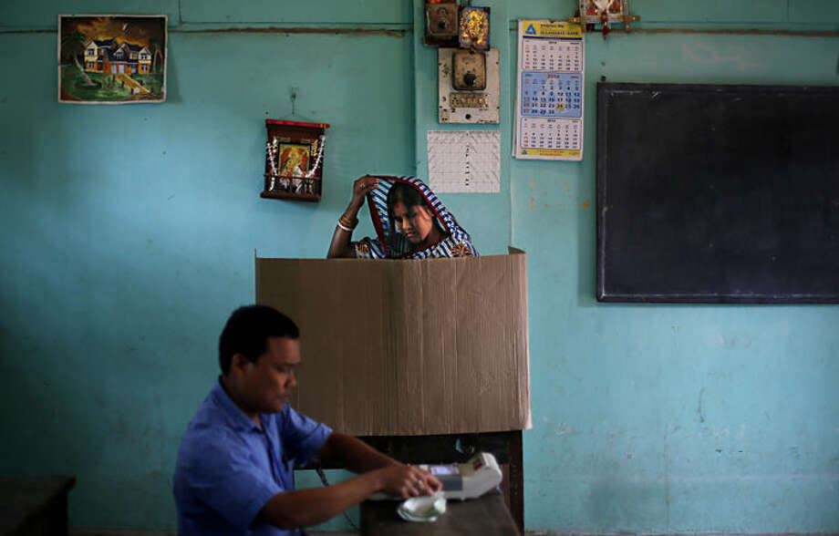 An Indian woman adjusts her sari as she casts her vote during the first phase of elections in Dibrugarh, in the northeastern state of Assam, India, Monday, April 7, 2014. Indians began voting Monday in the world's biggest election, with the opposition heading into the polls with strong momentum on promises of economic renewal. The country's 814 million eligible voters will vote in stages over the next five weeks. (AP Photo/Altaf Qadri)