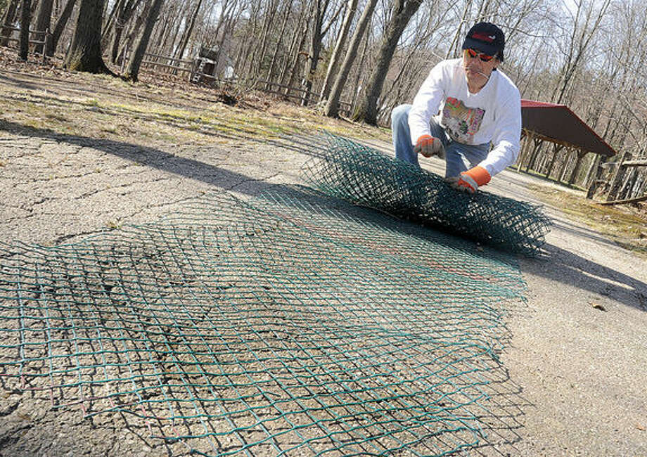 Volunteer Shin Miyoshi breaking down damaged fencing Sunday at the Camp Mahackeno Clean-Up Day in Westport. Hour photo/Matthew Vinci