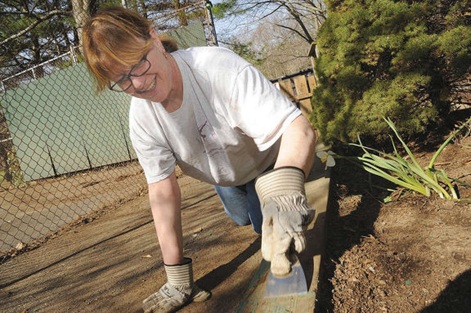 Volunteer Sally Silverstein scraping down old paint around the area of a flower bed Sunday at the Camp Mahackeno Clean-Up Day in Westport. Hour photo/Matthew Vinci