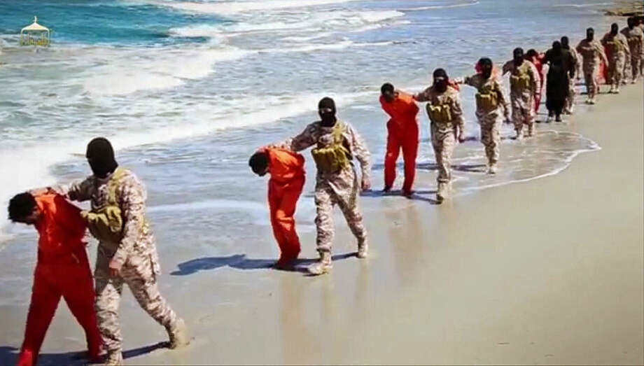 EDS NOTE: GRAPHIC CONTENT - This undated image made from a video released by Islamic State militants, Sunday, April 19, 2015, appears to show the killing of a group of captured Ethiopian Christians in Libya. The 29-minute video released online Sunday purportedly shows two groups of captives. It says one group is held by an IS affiliate in eastern Libya and the other by an affiliate in the south. A masked fighter delivers a long statement before the video switches between footage that purportedly shows the captives in the south being shot dead and the captives in the east being beheaded on a beach. (Militant video via AP)