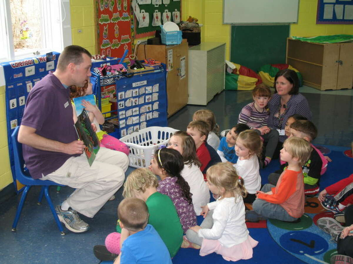 """To mark the """"Week of the Young Child,"""" Wilton Family Y staff member Aaron Britton is shown reading to a classroom of 4-year-olds who are in the Y's nursery school program. Several Y staff will be guest readers throughout the week to emphasize the importance of reading and the enjoyment of storytelling that enrich the lives of young children."""