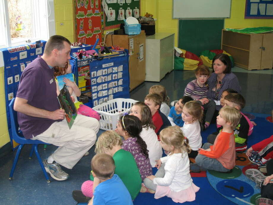 "To mark the ""Week of the Young Child,"" Wilton Family Y staff member Aaron Britton is shown reading to a classroom of 4-year-olds who are in the Y's nursery school program. Several Y staff will be guest readers throughout the week to emphasize the importance of reading and the enjoyment of storytelling that enrich the lives of young children."