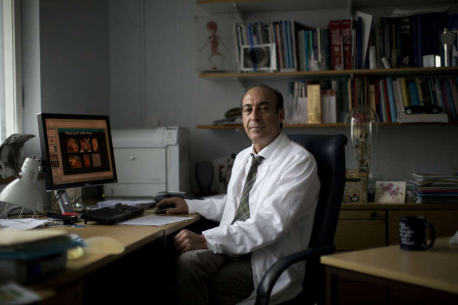"""Professor Alexander Seifalian poses for a portrait in his office at his research facility in the Royal Free Hospital in London, Monday, March 31, 2014. In the north London hospital, scientists are growing noses, ears and blood vessels in the laboratory in a bold attempt to make body parts using stem cells. It is among several labs around the world, including in the U.S., that are working on the futuristic idea of growing custom-made organs in the lab. While only a handful of patients have received the British lab-made organs so far— including tear ducts, blood vessels and windpipes — researchers hope they will soon be able to transplant more types of body parts into patients, including what would be the world's first nose made partly from stem cells. """"It's like making a cake,"""" said Alexander Seifalian at University College London, the scientist leading the effort. """"We just use a different kind of oven."""" (AP Photo/Matt Dunham)"""