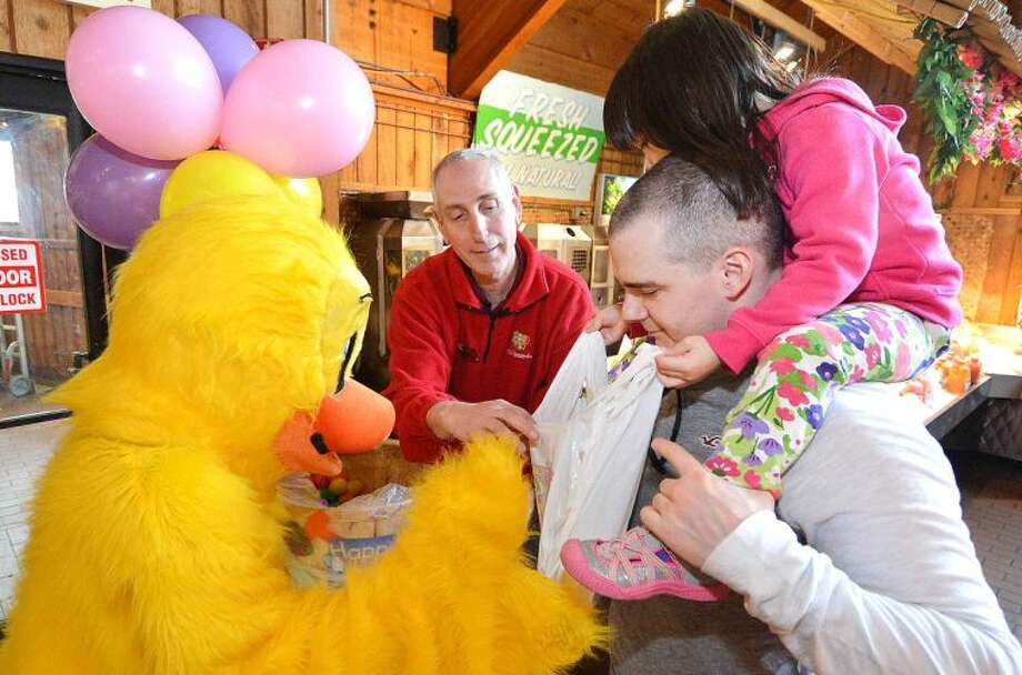 Hour Photo/Alex von Kleydorff 3yr old Aurora hall on the shoulders of dad Evan fill their bag with Easter Eggs from Daisy Duck during Stew Leonard's Eggs-Travaganza on Tuesday