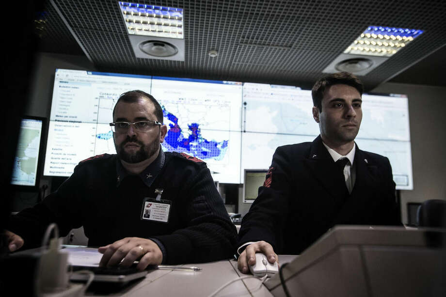Officers check monitors showing the ships navigating the area where the boat believed to be crowded with perhaps as many as 700 migrants capsized in the waters north of Libya, in the operation room of the Coast Guard during the coordination of rescue efforts, in Rome, Sunday, April 19, 2015. 28 migrants were rescued and at least 24 confirmed dead and sparking fears for what would be the Mediterranean's deadliest known migrant sea disaster, Italy's Coast Guard and humanitarian agency officials said Sunday. (Angelo Carconi/ANSA via AP) ITALY OUT