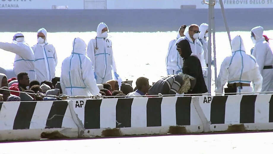 Migrants are seated, surrounded by emergency relief workers aboard a vessel at the Italian port of Messina, Saturday April 18, 2015, as migrants prepare to be processed at the quayside. UNHCR says Sunday, April 19, 2015, the search and recovery rescue operation is under way after a boat carrying migrants overturned north of Libya. (AP Photo/AP TV)