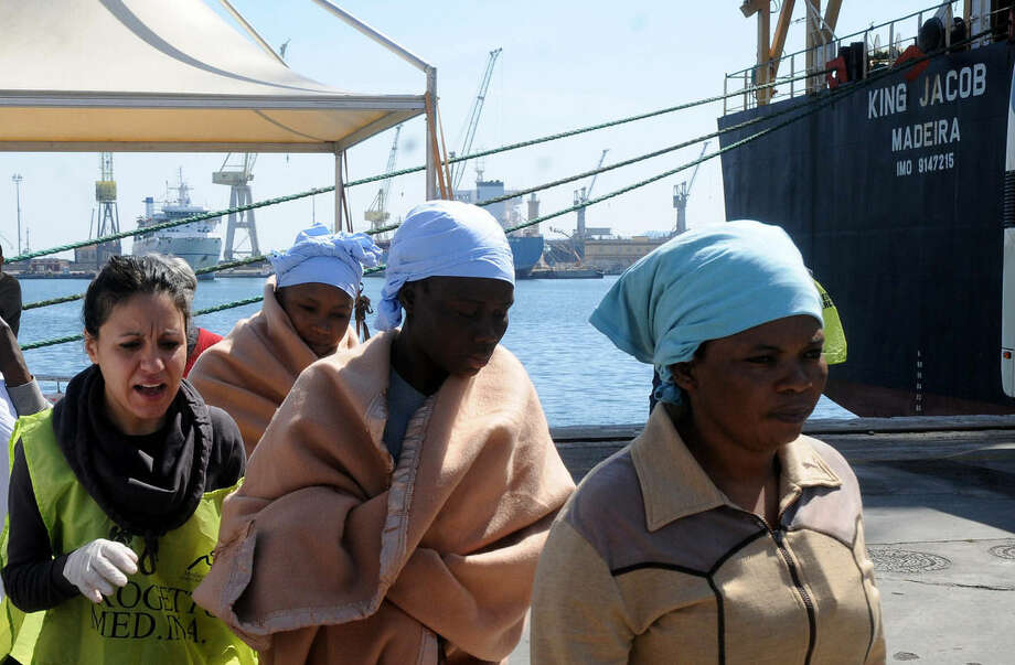 In this photo taken at the Palermo harbor on April 15 and made available Sunday, April 19, migrants receive relief after disembarking in Palermo, Sicily, Italy. In background, right, is harbored the King Jacob Portuguese cargo vassel, the first ship to arrive near a boat believed to be crowded with 700 migrant in distress, only to see it capsizing in the waters north of Libya, Sunday, April 19, 2015. 24 migrants were confirmed dead, sparking fears for what could become the Mediterranean's deadliest known migrant sea disaster, Italy's Coast Guard and other officials said Sunday. (AP Photo/Alessandro Fucarini)