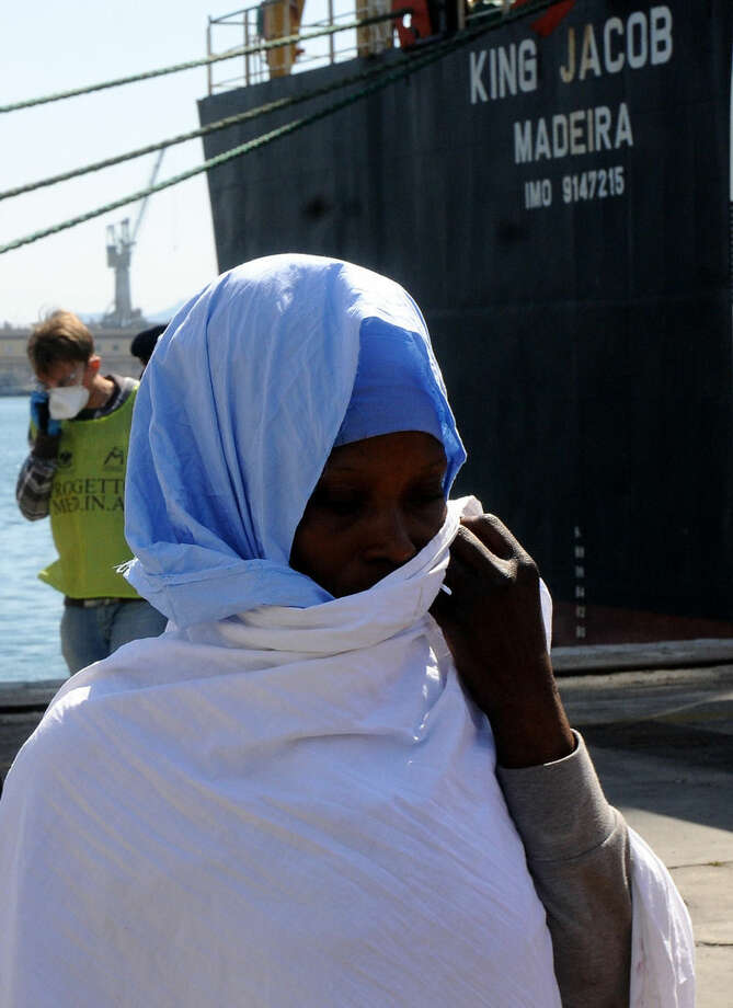 In this photo taken at the Palermo harbor on April 15 and made available Sunday, April 19, a migrants stands after disembarking in Palermo, Sicily, Italy. In background, right, is harbored the King Jacob Portuguese cargo vassel, the first ship to arrive near a boat believed to be crowded with 700 migrant in distress, only to see it capsizing in the waters north of Libya, Sunday, April 19, 2015. 24 migrants were confirmed dead, sparking fears for what could become the Mediterranean's deadliest known migrant sea disaster, Italy's Coast Guard and other officials said Sunday. (AP Photo/Alessandro Fucarini)