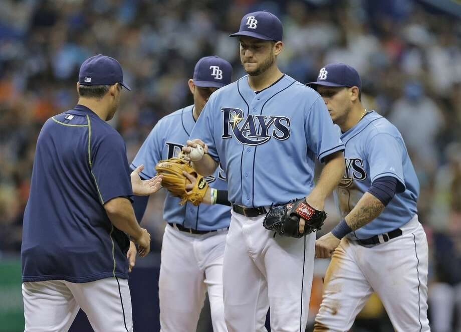 Tampa Bay Rays starting pitcher Matt Andriese, center, hands the ball to manager Kevin Cash, left, as he is taken out of a baseball game against the New York Yankees during the fourth inning Sunday, April 19, 2015, in St. Petersburg, Fla. (AP Photo/O'Meara)