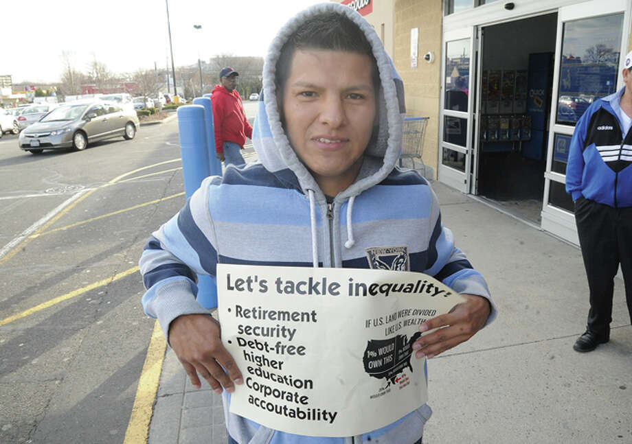 Cesar Fernandez among protestors Tuesday at the Walmart on Connecticut Avenue where supporters of a statewide day of action gathered to highlight growing inequality in Connecticut. Hour photo/Matthew Vinci