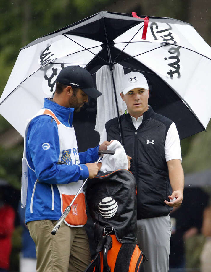 Jordan Spieth and his caddie Michael Greller, left, discuss his shot on the second tee during the final round of the RBC Heritage golf tournament in Hilton Head Island, S.C., Sunday, April 19, 2015. (AP Photo/Stephen B. Morton)