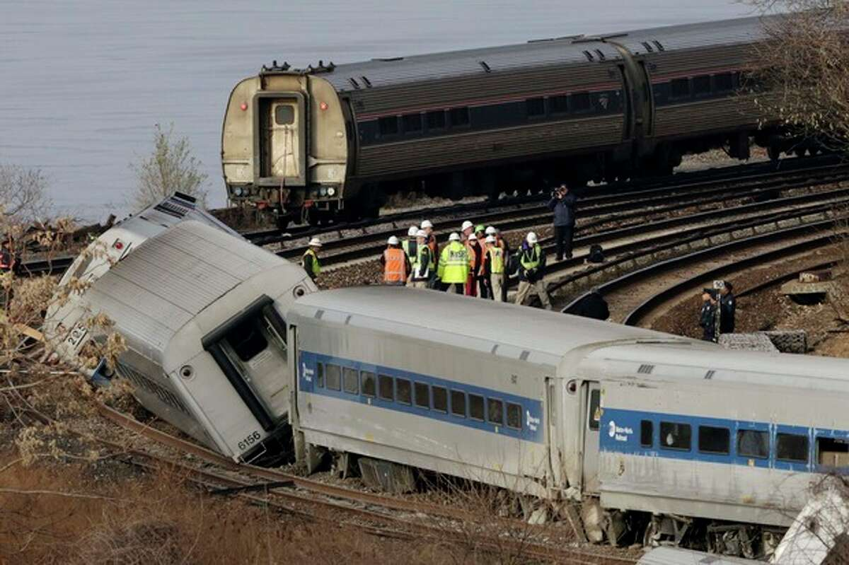 FILE- In this Dec. 1, 2013 file photo, an Amtrak train, top, traveling on an unaffected track, passes a derailed Metro-North commuter train in the Bronx borough of New York. Metro-North trains are equipped with an automatic breaking system that might have prevented the crash, but it was configured to mainly to keep trains at a safe distance from one another, not to enforce speed limits on curves, hills or bridges. Four people died when the Metro-North commuter train failed to slow as it approached a tight curve in the Bronx. (AP Photo/Mark Lennihan, File)