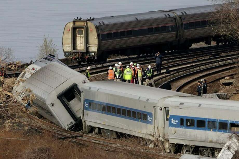 FILE- In this Dec. 1, 2013 file photo, an Amtrak train, top, traveling on an unaffected track, passes a derailed Metro-North commuter train in the Bronx borough of New York. Metro-North trains are equipped with an automatic breaking system that might have prevented the crash, but it was configured to mainly to keep trains at a safe distance from one another, not to enforce speed limits on curves, hills or bridges. Four people died when the Metro-North commuter train failed to slow as it approached a tight curve in the Bronx. (AP Photo/Mark Lennihan, File) / AP