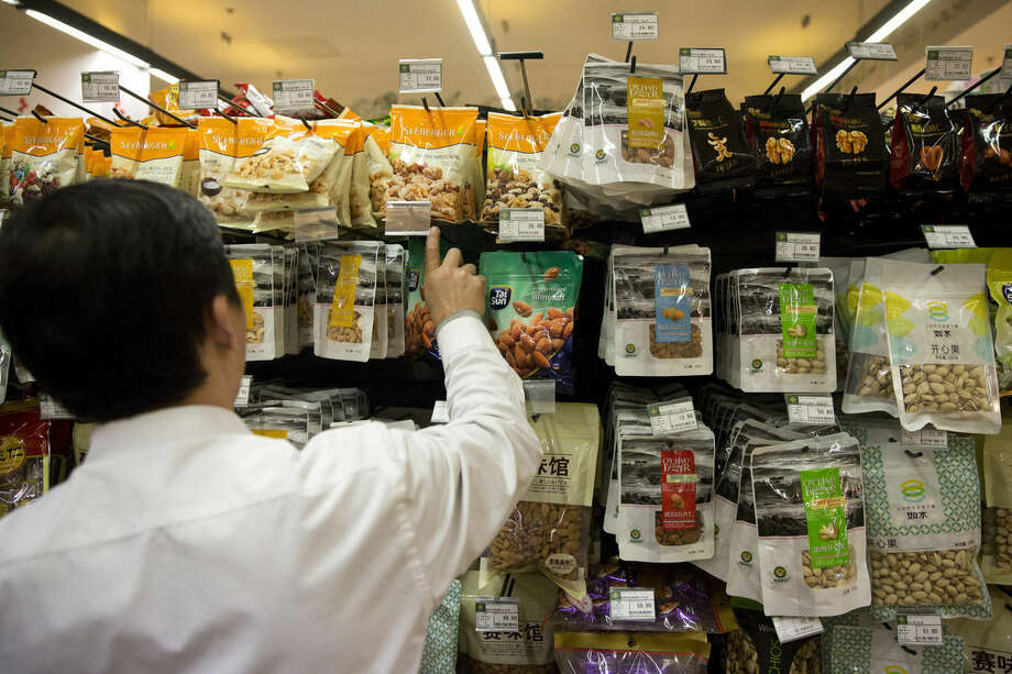 In this Thursday, April 9, 2015 photo, a worker stocks up on almonds packaged as originating from the United States at a supermarket in Beijing. Last year almond orchards consumed more of California's vanishing water than the indoor use of all 39 million California residents combined. As California enters its fourth year of drought, and imposes the first mandatory statewide water cutbacks on cities and towns, the $6.5 billion almond crop is helping drive a sharp debate about water use, agricultural interests and how both affect the state's giant economy. (AP Photo/Ng Han Guan)