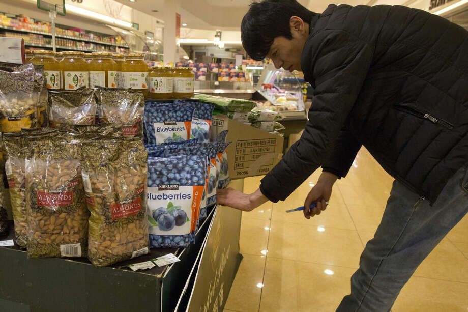 In this Thursday, April 9, 2015 photo, a worker replaces advertisement near bags of almonds packaged as originating from California at a supermarket in Beijing. Last year almond orchards consumed more of California's vanishing water than the indoor use of all 39 million California residents combined. As California enters its fourth year of drought, and imposes the first mandatory statewide water cutbacks on cities and towns, the $6.5 billion almond crop is helping drive a sharp debate about water use, agricultural interests and how both affect the state's giant economy. (AP Photo/Ng Han Guan)