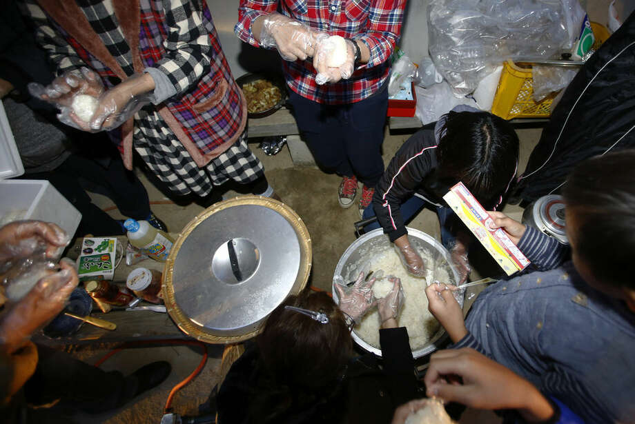 Evacuees make rice balls for dinner at a public park in Ozu, Kumamoto, southern Japan, Saturday, April 16, 2016. After two nights of earthquakes flattened houses and triggered major landslides in southern Japan, dozens of residents of the town of Ozu have slept in their cars at a public park. (AP Photo/Shizuo Kambayashi)