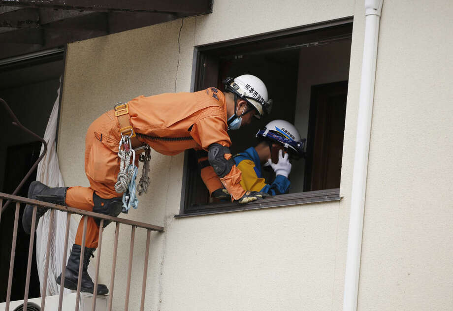 Rescue workers search for Yumiko Yamauchi, 93, at her collapsed house in Mashiki, Kumamoto prefecture, southern Japan, Saturday, April 16, 2016. Powerful earthquakes a day apart shook southwestern Japan, trapping many beneath flattened homes and sending thousands to seek shelter in gymnasiums and hotel lobbies. Yamauchi was trapped in her bedroom as the upper floor collapsed over her in an earthquake. (AP Photo/Koji Ueda)