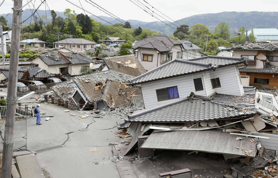 Damaged houses sit after an earthquake in Mashiki, Kumamoto prefecture, southern Japan Saturday, April 16, 2016. Powerful earthquakes a day apart shook southwestern Japan, as thousands of army troops and other rescuers on Saturday rushed to save scores of trapped residents before weather turns bad. (Kyodo News via AP) JAPAN OUT, MANDATORY CREDIT