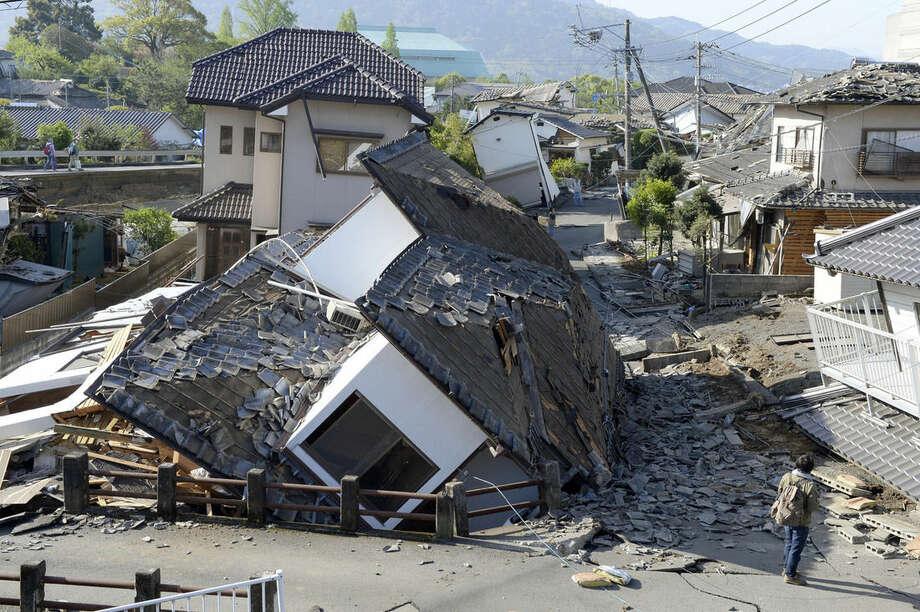 Houses are seen destroyed after an earthquake in Mashiki, Kumamoto prefecture, southern Japan Saturday, April 16, 2016. A powerful earthquake struck southern Japan early Saturday, barely 24 hours after a smaller quake hit the same region. (Ryosuke Uematsu/Kyodo News via AP) JAPAN OUT, MANDATORY CREDIT
