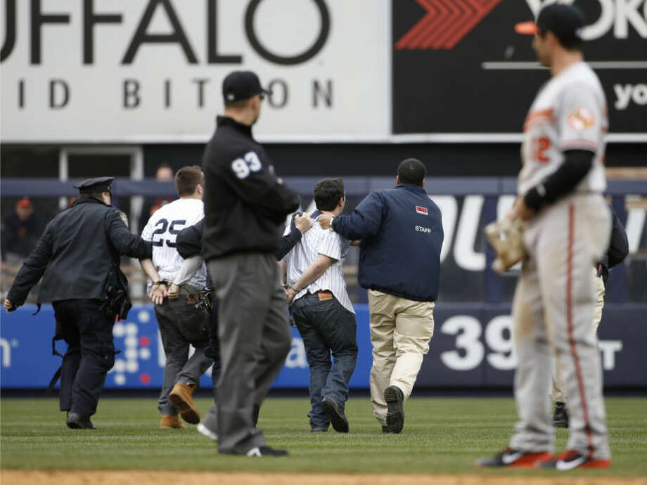 Baltimore Orioles second baseman Stephen Lombardozzi (12) watches as police and security officers escort two fans away after the fans interrupted play by running onto the field in the eighth inning of the Yankees 14-5 loss to the Orioles in a baseball game at Yankee Stadium in New York, Tuesday, April 8, 2014. (AP Photo/Kathy Willens)