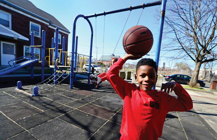 Seven year old Calvin Talbert, a tenant of the oldest public housing in Connecticut, Washington Village, plays in the housing project's playground on Wednesday, April 20, 2016. The New Britain Superior Court dismissed the Friends of Ryan Park appeal of The Connecticut Department of Energy and Environmental Protection decision allowing the proposed reconstruction of Washington Village to proceed.