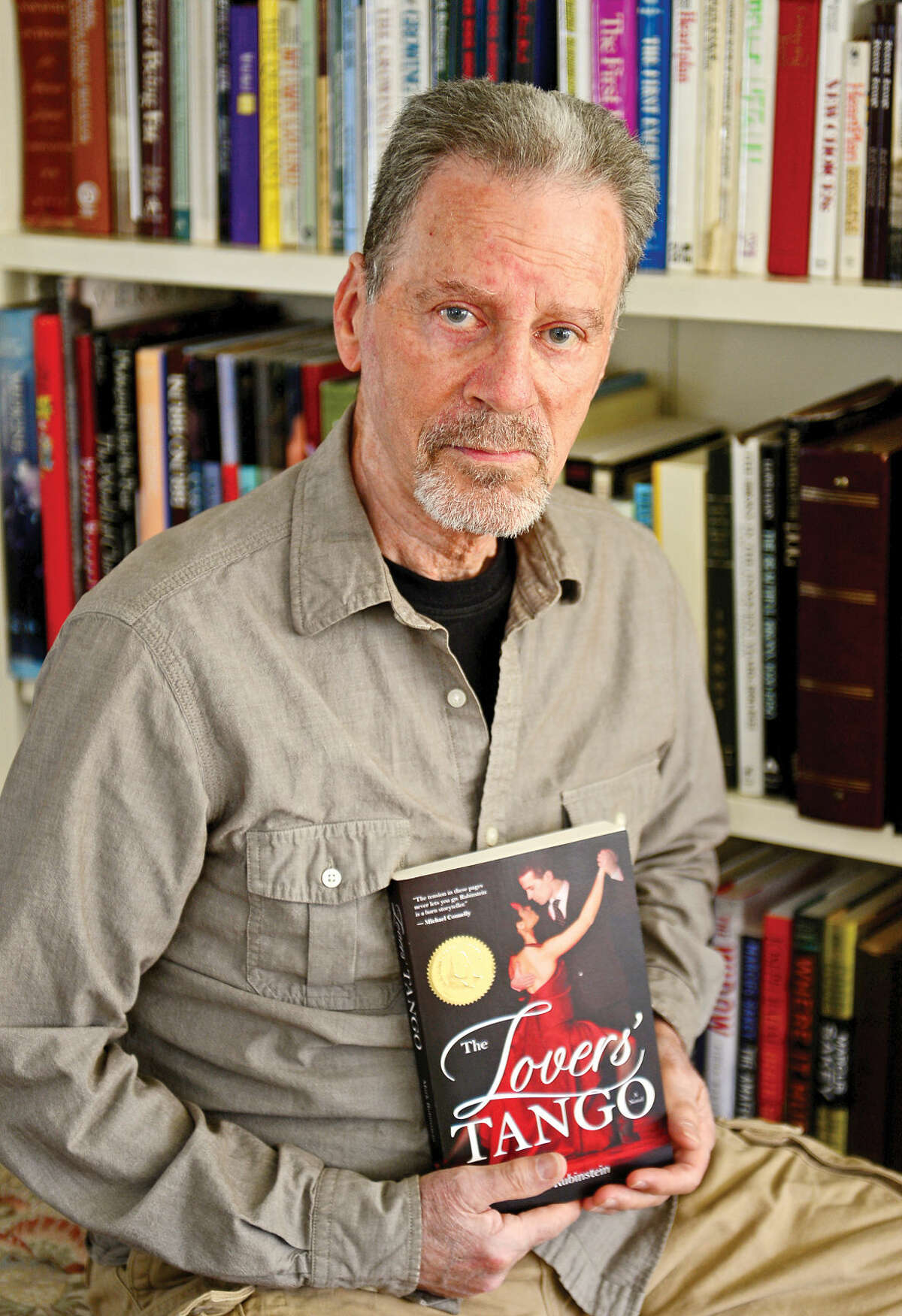 """Author Mark Rubinstein in his Wilton home with his latest book, """"The Lover's Tango,"""" Thursday, April 21, 2016. Rubinstein abandoned his psychiatric career four years ago so that he could pursue his dream of writing professionally."""