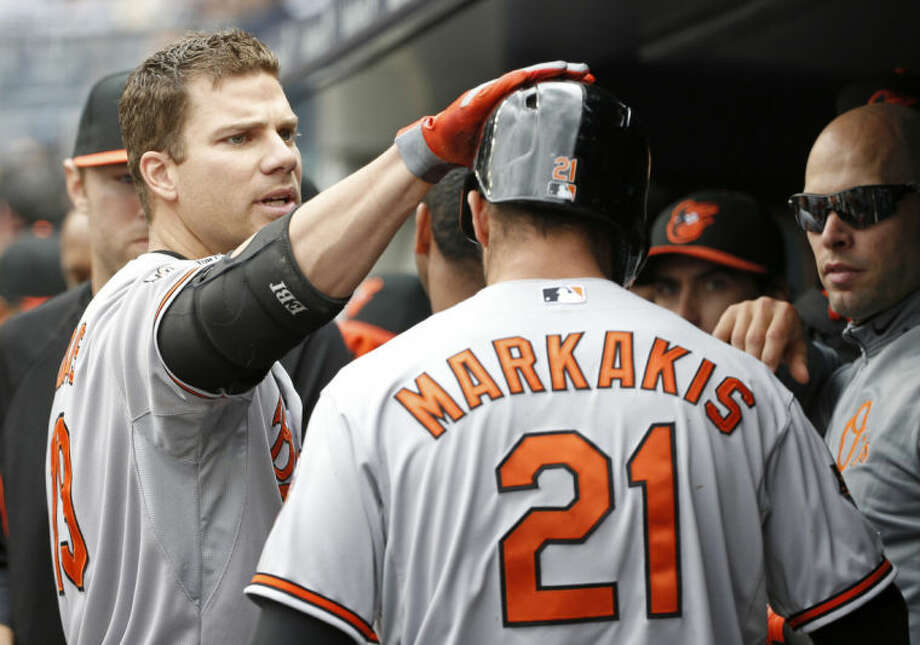 Baltimore Orioles Chris Davis pats the Orioles Nick Markakis (21) on the helmet after Markakis scored on Davis's first inning sacrifice fly in the Orioles 14-5 victory over the New York Yankees in an MLB American League baseball game at Yankee Stadium in New York, Tuesday, April 8, 2014. (AP Photo/Kathy Willens)