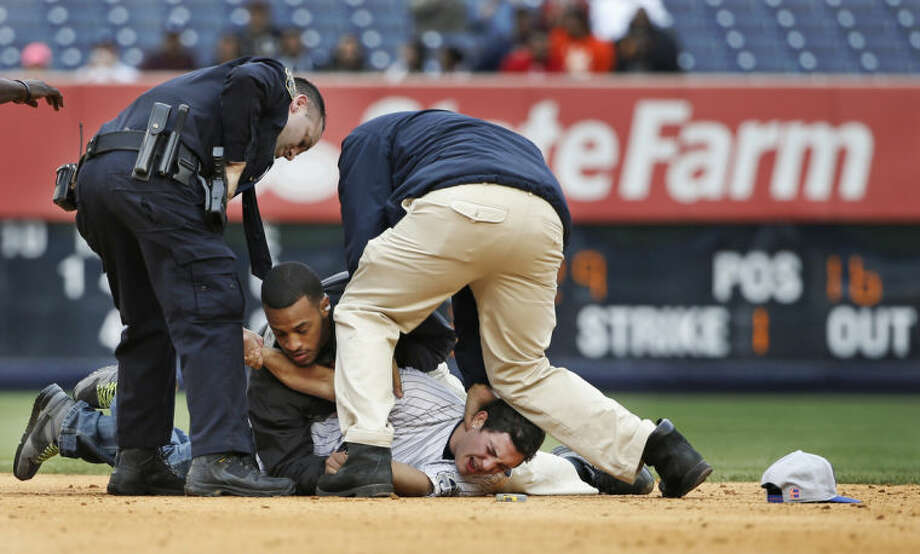 A police officer and two stadium security officers tackle a fan who ran onto the field in the eighth inning of the Yankees 14-5 loss to the Baltimore Orioles in the MLB American League baseball game at Yankee Stadium in New York, Tuesday, April 8, 2014. Two fans made it onto the field behind second base in the incident, which interrupted play. Both fans were tackled and escorted off the field as players watched. (AP Photo/Kathy Willens)