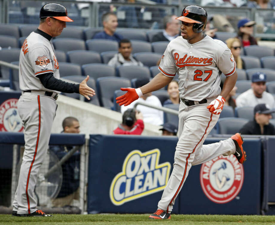 Baltimore Orioles third base coach Bobby Dickerson congratulates Delmon Young, right, after Young's sixth-inning, two-run home run off New York Yankees starting pitcher Vidal Nuno in a baseball game at Yankee Stadium in New York, Tuesday, April 8, 2014. (AP Photo/Kathy Willens)