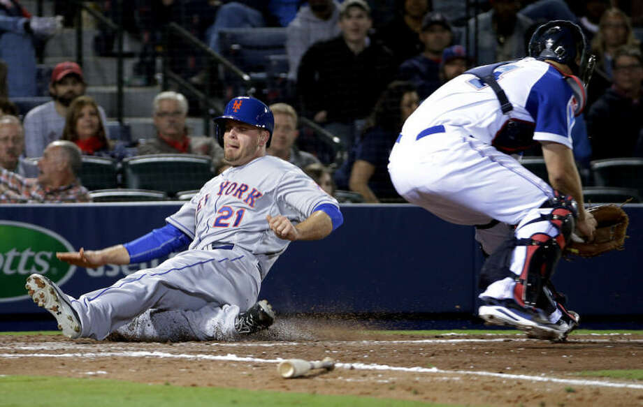 New York Mets' Lucas Duda, left, slides past the tag of Atlanta Braves catcher Evan Gattis to score off a single by teammate Ruben Tejada in the eighth inning of baseball game, Tuesday, April 8, 2014, in Atlanta. (AP Photo/David Goldman)
