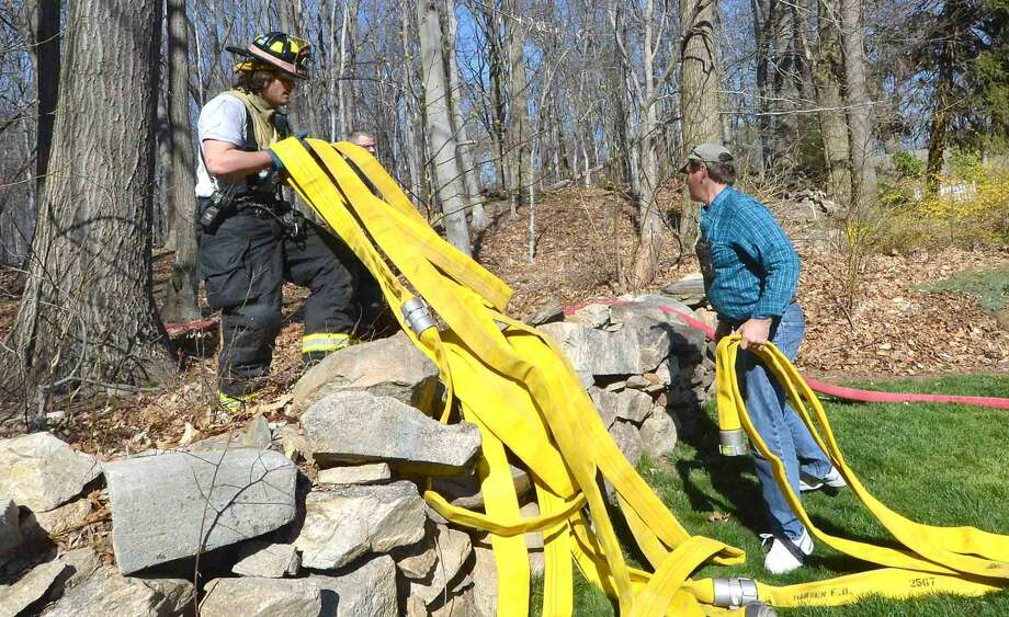 Volunteer Firefighters from Noroton Heights and Darien pull some more fire hose over a stone wall to battle a fire in Woodland Park in Darien Conn. on Wednesday April 20 2016