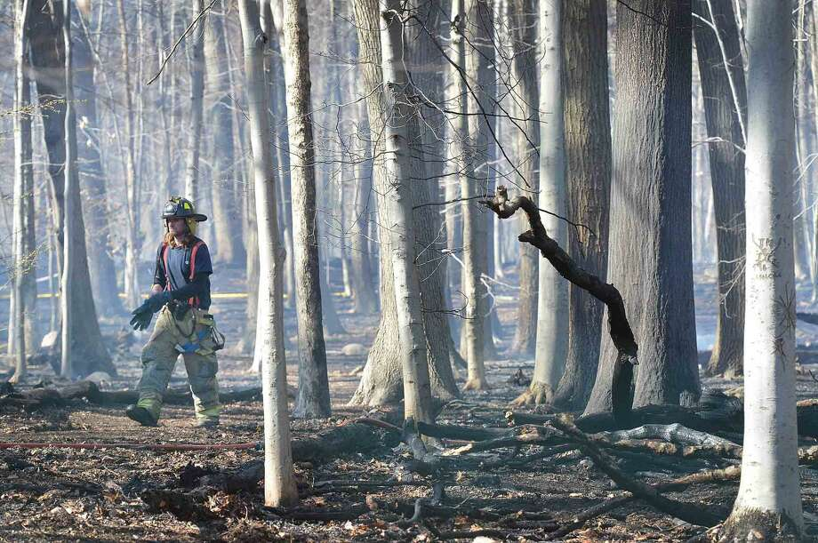 Volunteer Firefighters from Noroton Heights and Darien battle a fast moving fire in Woodland Park in Darien Conn. on Wednesday April 20 2016