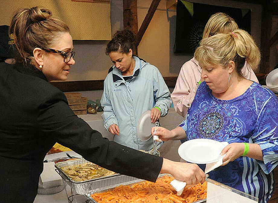 Diane Pane with Wilton Pizza serves up favorites from the menu to Melissa Mednickat the 2015 Taste of Wilton held at the Wilton Historical Society on Monday. Photo/Matthew Vinci