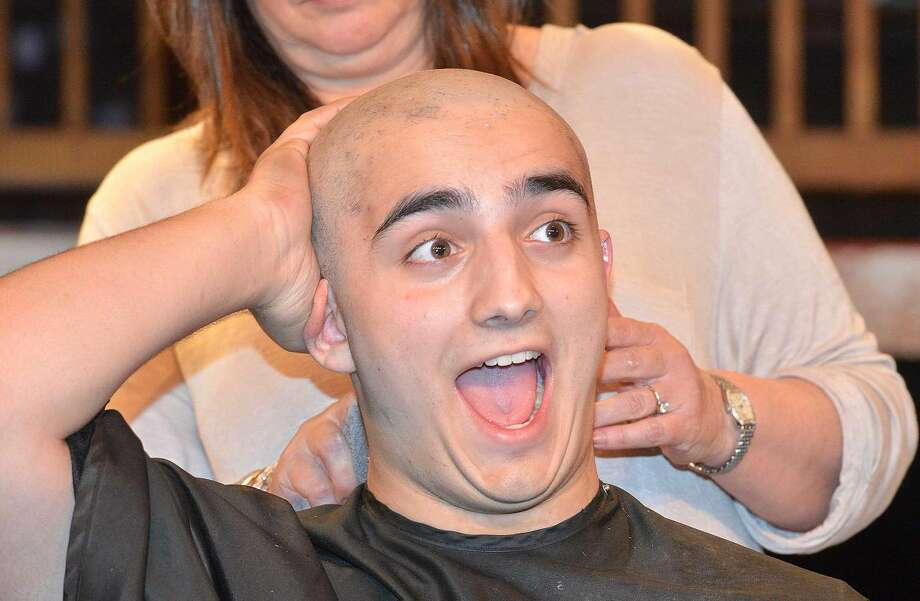 Hour Photo/Alex von Kleydorff Norwalk High School student Sam Patterson reacts as he feels his clean shaven head after stylist Patty Gurnari cut all his hair then shaved his head. Sam is preparing for the role of Big Daddy Warbucks in the schools prodution of Annie but also to benefit St. Baldricks