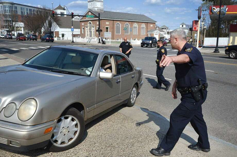 Hour Photo/Alex von Kleydorff Norwalk Police Officers direct a car out of traffic on West Ave as Officer Jamile Wright points the driver into a parking lot and will issue her a ticket for distracted driving