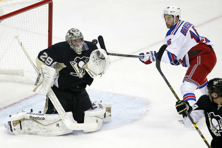 Pittsburgh Penguins goalie Marc-Andre Fleury (29) blocks a shot and New York Rangers' Derick Brassard (16) can't get his stick on the rebound during the first period of a first-round NHL playoff hockey game in Pittsburgh Monday, April 20, 2015.(AP Photo/Gene J. Puskar)