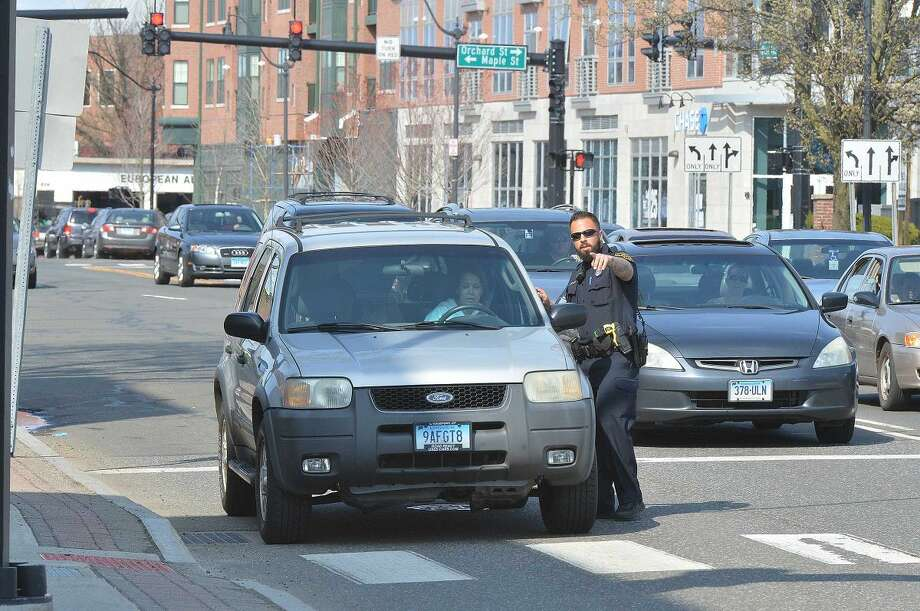 Hour Photo/Alex von Kleydorff Norwalk Police Officers Norwalk Police Officer David Geismar points a motorist to pull over after she was observed by an officer one block north, on West Ave. on her cell phone during distracted driving enforcement on Tuesday