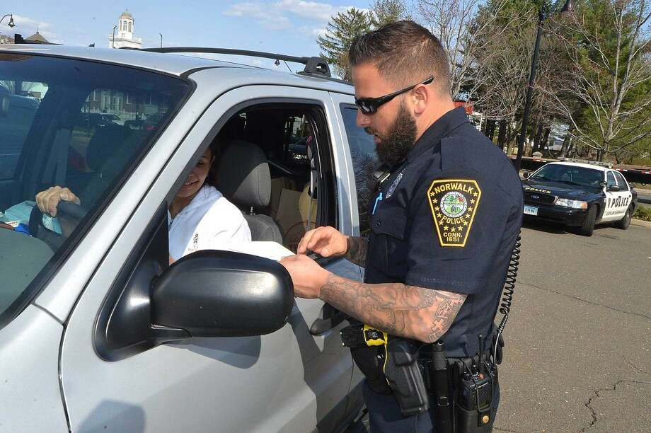 Hour Photo/Alex von Kleydorff Norwalk Police Officers Norwalk Police Officer David Geismar issues a ticket to a driver after she was observed by an officer stationed one block north, on West Ave. on her cell phone during distracted driving enforcement on Tuesday