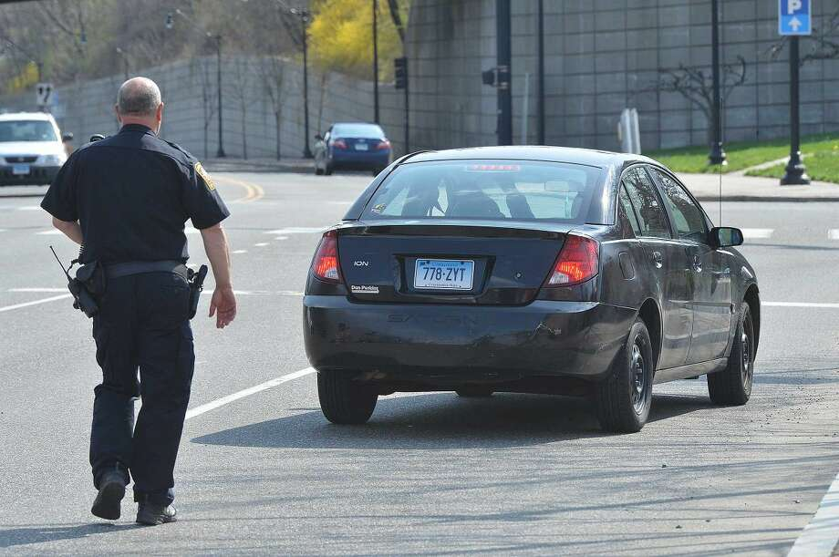 Hour Photo/Alex von Kleydorff Norwalk Police Officer Russell Ouelette walks up to a vehicle that didnt pull over when prompted during distracted driving enforcement along West Ave. on Tuesday