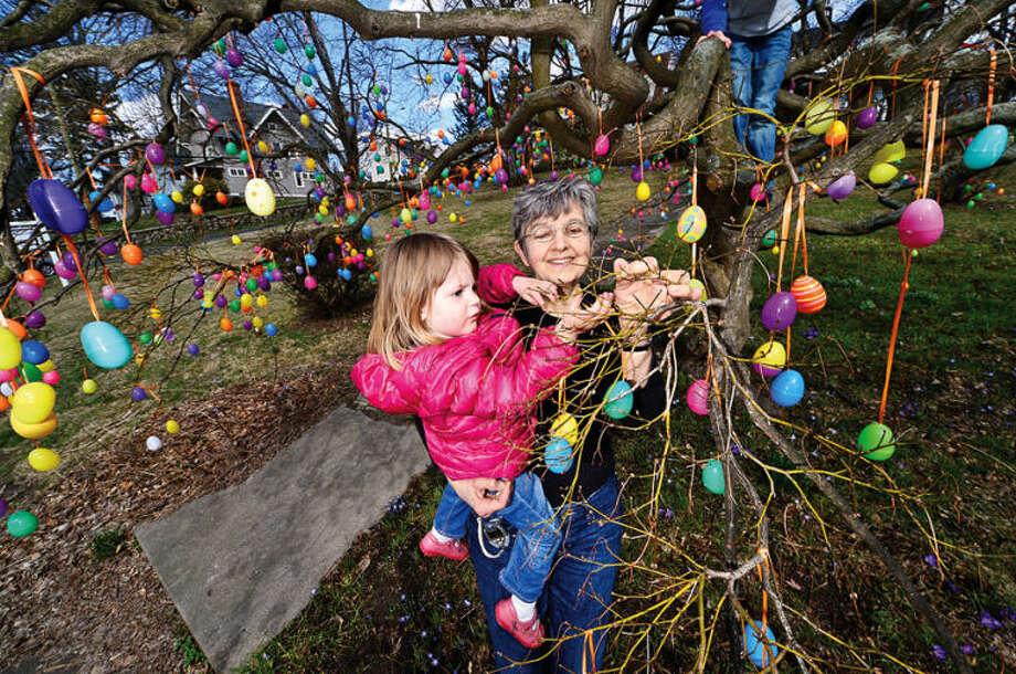 Hour photo / Erik Trautmann Jalna Jaeger and her granddaughter Emma Garnett, 3, decorate Jaeger's Easter Egg Tree at her home on East Ave. Wednesday.