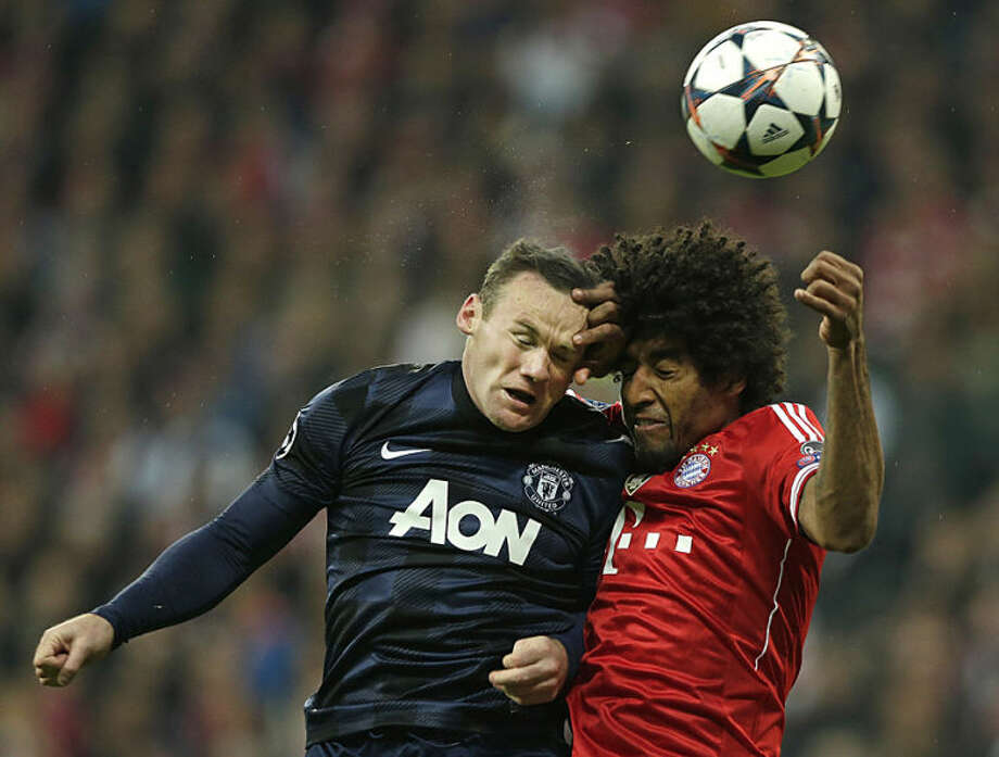 Manchester United's Wayne Rooney, left, battles for the ball with Bayern's Dante during the Champions League quarterfinal second leg soccer match between Bayern Munich and Manchester United in the Allianz Arena in Munich, Germany, Wednesday, April 9, 2014. (AP Photo/Matthias Schrader)