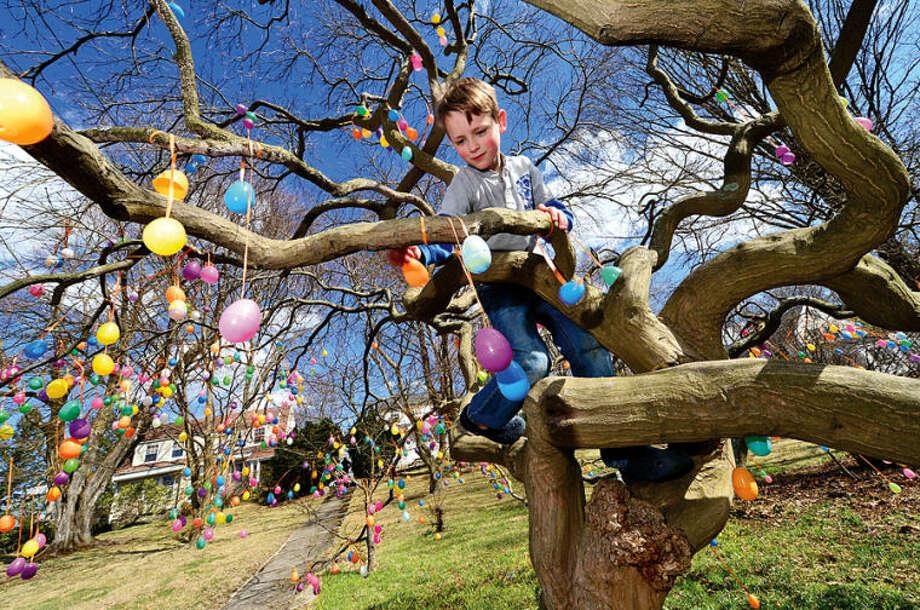 Hour photo / Erik Trautmann Jackson Garnett, 7, helps his grandmother, Jalna Jaeger decorate her Easter Egg Tee on East Ave Wednesday.
