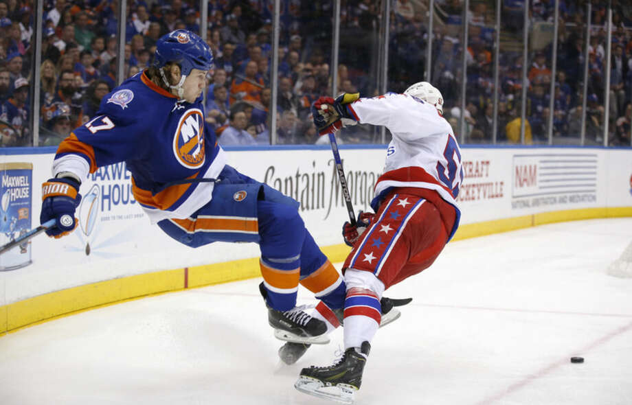 New York Islanders left wing Matt Martin (17) trips on Washington Capitals defenseman Mike Green (52) in the second period of Game 4 of a first-round NHL Stanley Cup hockey playoff series at Nassau Coliseum in Uniondale, N.Y., Tuesday, April 21, 2015. (AP Photo/Kathy Willens)