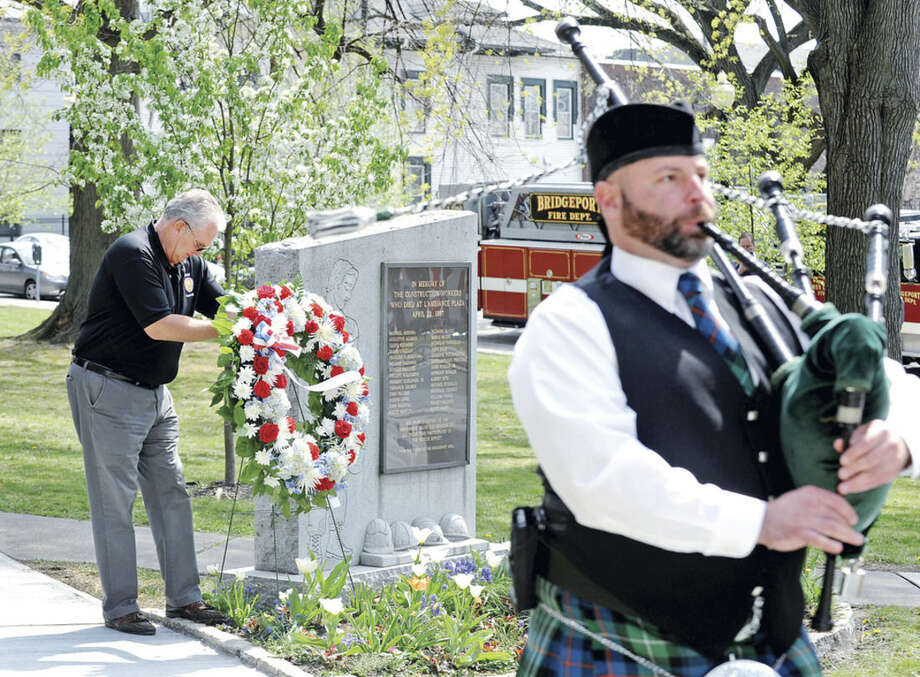 Charlie Carrol places a memorial wreath at the monument honoring the 28 construction workers that died in the collapse of the L'Ambiance Plaza in Bridgeport, Conn. 29 years ago. The annual remembrance ceremony was held Friday, April 22, 2016 at the Bridgeport City Hall plaza. Joseph C. Lowe, 54, of Norwalk died in the disaster.