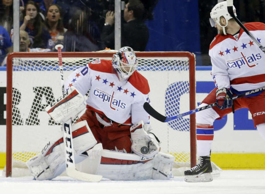 Washington Capitals goalie Braden Holtby (70) makes a save in the first period of Game 4 of a first-round NHL Stanley Cup hockey playoff series against the New York Islanders at Nassau Coliseum in Uniondale, N.Y., Tuesday, April 21, 2015. (AP Photo/Kathy Willens)