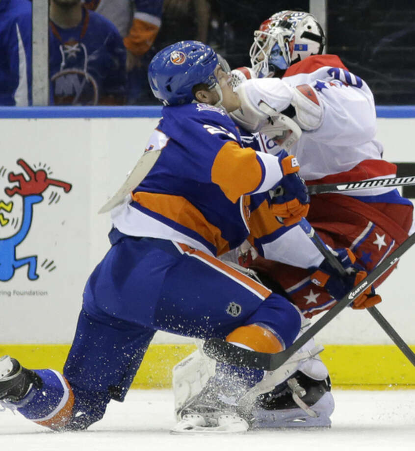 Washington Capitals goalie Braden Holtby (70) collides with New York Islanders center Anders Lee (27) in the first period of Game 4 of a first-round NHL Stanley Cup hockey playoff series at Nassau Coliseum in Uniondale, N.Y., Tuesday, April 21, 2015. (AP Photo/Kathy Willens)