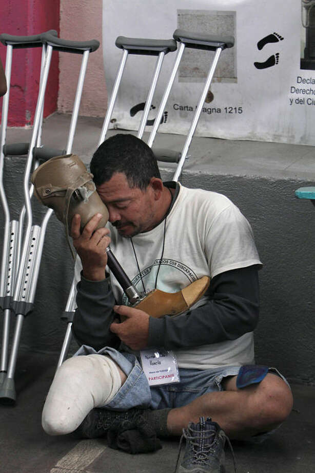 Norman Saul Varela, 46, a migrant from Honduras who uses a prosthetic leg after loosing his limb in 2005 while riding the train through Mexico toward the U.S. border, embraces his prosthetic leg after taking it off while explaining to journalists his ordeal at a migrant shelter in Mexico City, Wednesday, April 9, 2014. Varela is in Mexico City, along with other Honduran migrants who lost limbs after falling from trains during northbound journeys across Mexico, to ask the country's Senate to stop the government's persecution of Central Americans and protect them from criminal gangs. (AP Photo/Marco Ugarte)