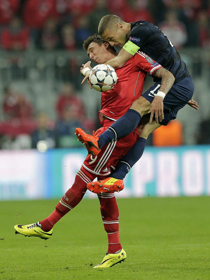 Manchester United's Nemanja Vidic, right, climbs on top of Bayern's Mario Mandzukic during the Champions League quarterfinal second leg soccer match between Bayern Munich and Manchester United in the Allianz Arena in Munich, Germany, Wednesday, April 9, 2014. (AP Photo/Matthias Schrader)